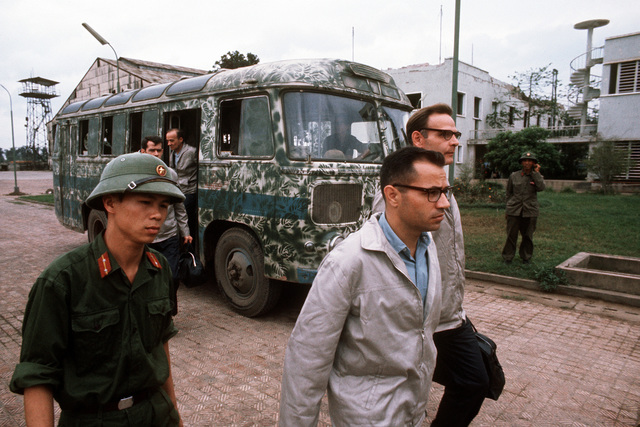 Prisoners of war disembark a bus at Gia Lam Airport. The men will board a C-141 Starlifter aircraft for evacuation to Clark Air Base, Republic of the Philippines