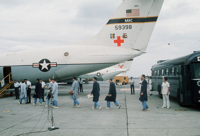 A line of returned POWs from Viet Cong and North Vietnamese prisons walk from buses to the waiting C-141 Starlifter for the trip to the states. After their release they were flown to Clark AB hospital for medical checkups