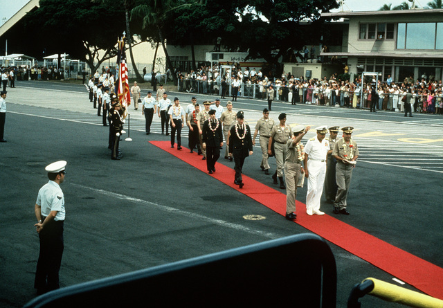 After a brief refueling stop, the first group of Prisoners of War released in Hanoi by North Vietnam walk on the red carpet toward their waiting aircraft. They are lead by Pacific Command's officials and POW, U.S. Navy CPT Jeremiah Andrew Denton, (Captured 18 Jul65). The POWs were enroute from Clark Air Base, Philippines to Travis Air Force Base, CA and then to be reunited with their families in the states