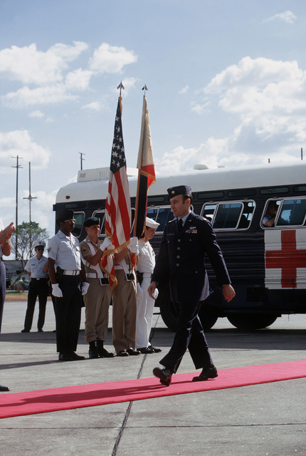 An unidentified U.S. Air Force Major and former Prisoner of War walks the red carpet, past the honor guard, to the plane that will return him to the United States