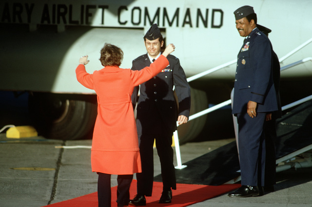 """As MGEN Daniel """"Chappie"""" James looks on, former POW and U.S. Air Force 1ST LT William Youl Arcorui (Captured 22 Dec 72) greets his wife after his arrival on the C-141 Starlifter from Clark Air Base. LT Arcorui was in the first group of POWs released by the North Vietnamese government in Hanoi"""