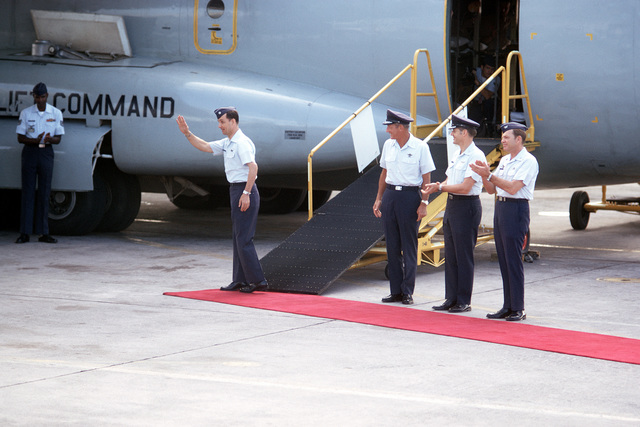 Ex-POW and unidentified U.S. Air Force LCOL waves to the crowd of well wishers prior to boarding the C-141 Starlifter for the flight to the United States. Standing to the right is 13th Air Force Commander, LGEN William G. Moore Jr., COL John W. Ord, Commander, Clark Hospital and COL Raymond G. Lawry, Deputy Site Commander, Joint Homecoming Reception Center