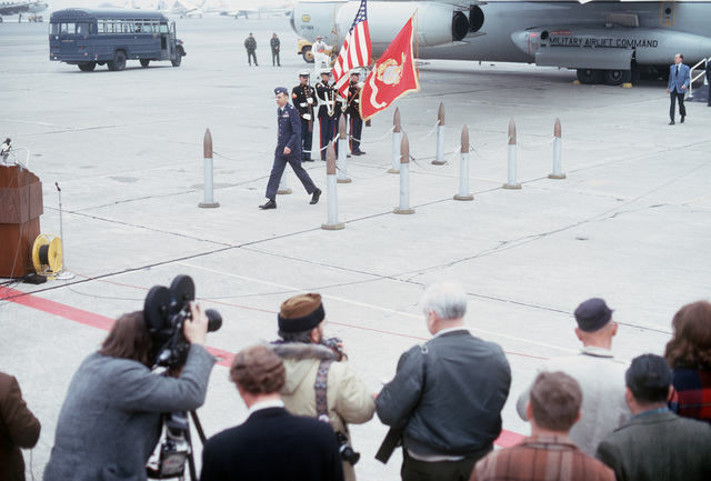Former POW and U.S. Air Force COL Albert Edward Runyan walks from the C-141 Starlifter to the waiting microphones. COL Runyan was captured on 29 Apr 66 and released by the North Vietnamese in Hanoi 12 Feb 73