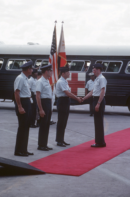 Former POW and U.S. Air Force COL David Burnett Hatcher shakes hands with COL Raymond G. Lawry, Deputy Site Commander, Joint Homecoming Reception Center, waiting is COL John W. Ord, Clark Hospital Commander and LGEN William G. Moore, Commander 13th Air Force is on far left. LCOL Hatcher was captured on 30 May 66 and was released in Hanoi by the North Vietnamese on 12 Feb 73