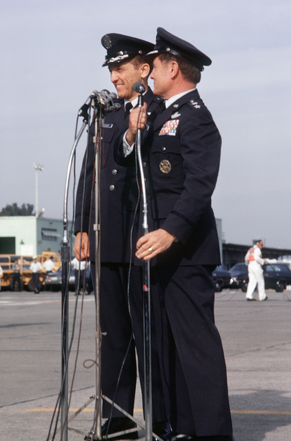 Former POW and U.S. Air Force COL Robinson Risner, at the microphone, express his thanks to the crowd and press upon arriving on a flight from Clark Air Base. 22nd Air Force Commander, MGEN John Gonge stands behind COL Risner. COL Risner was captured on 16 Sep 65 and released by North Vietnamese in Hanoi on 12 Feb 73