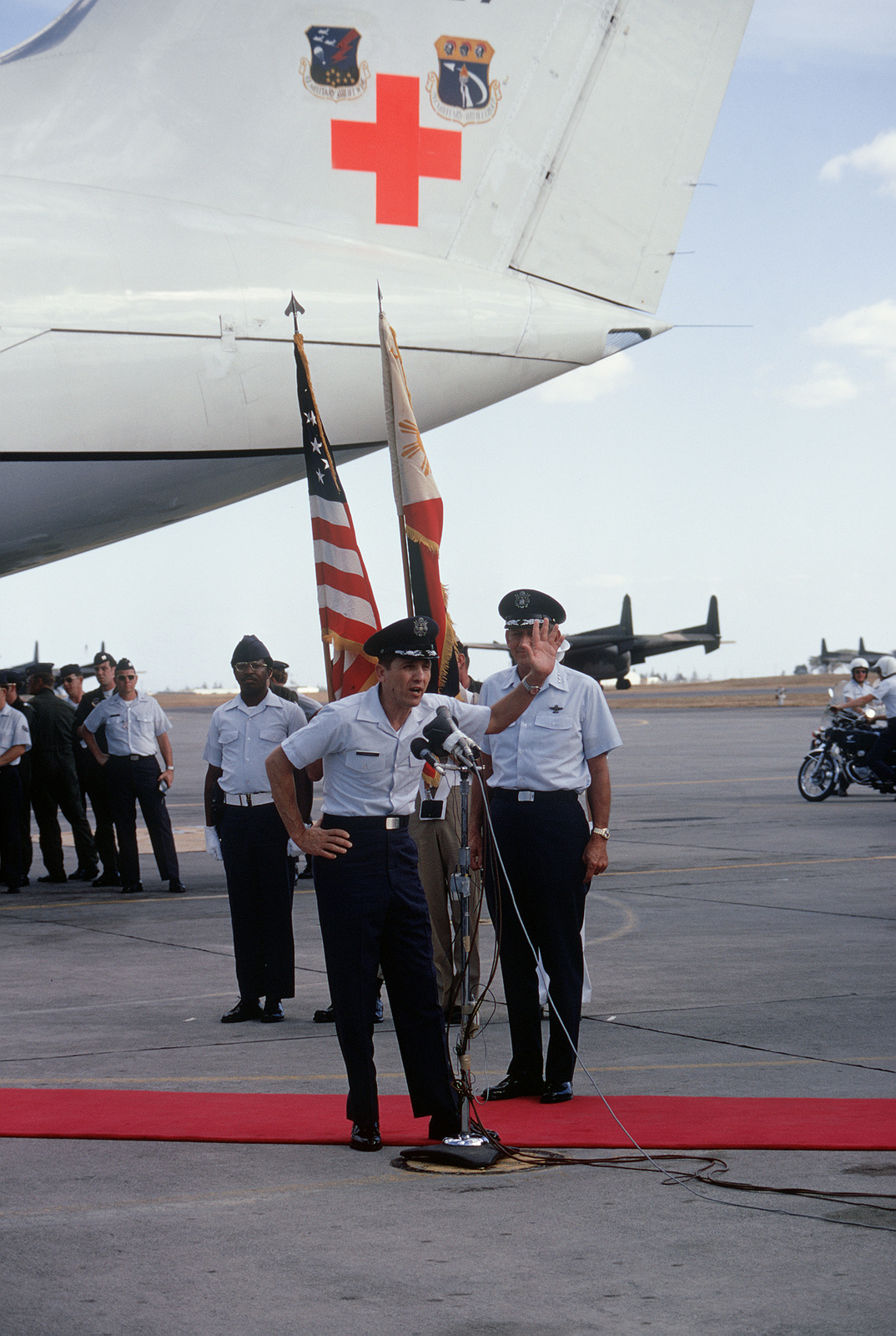 Former POW and U.S. Air Force COL Robinson Risner, at the microphone, waves and thanks the crowd and press prior to boarding the waiting C-141 Starlifter for the flight to the states. Standing behind COL Risner is LGEN William G. Moore, Commander 13th Air Force. COL Risner was captured on 16 Sep 65 and released by the North Vietnamese in Hanoi on 12 Feb 73