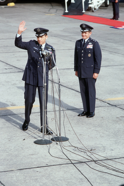 Former POW and U.S. Air Force COL Robinson Risner, at the microphone, waves his thanks to the crowd and press upon arriving on a flight from Clark Air Base. 22nd Air Force Commander, MGEN John Gonge stands behind COL Risner. COL Risner was captured on 16 Sep 65 and released by North Vietnamese in Hanoi on 12 Feb 73