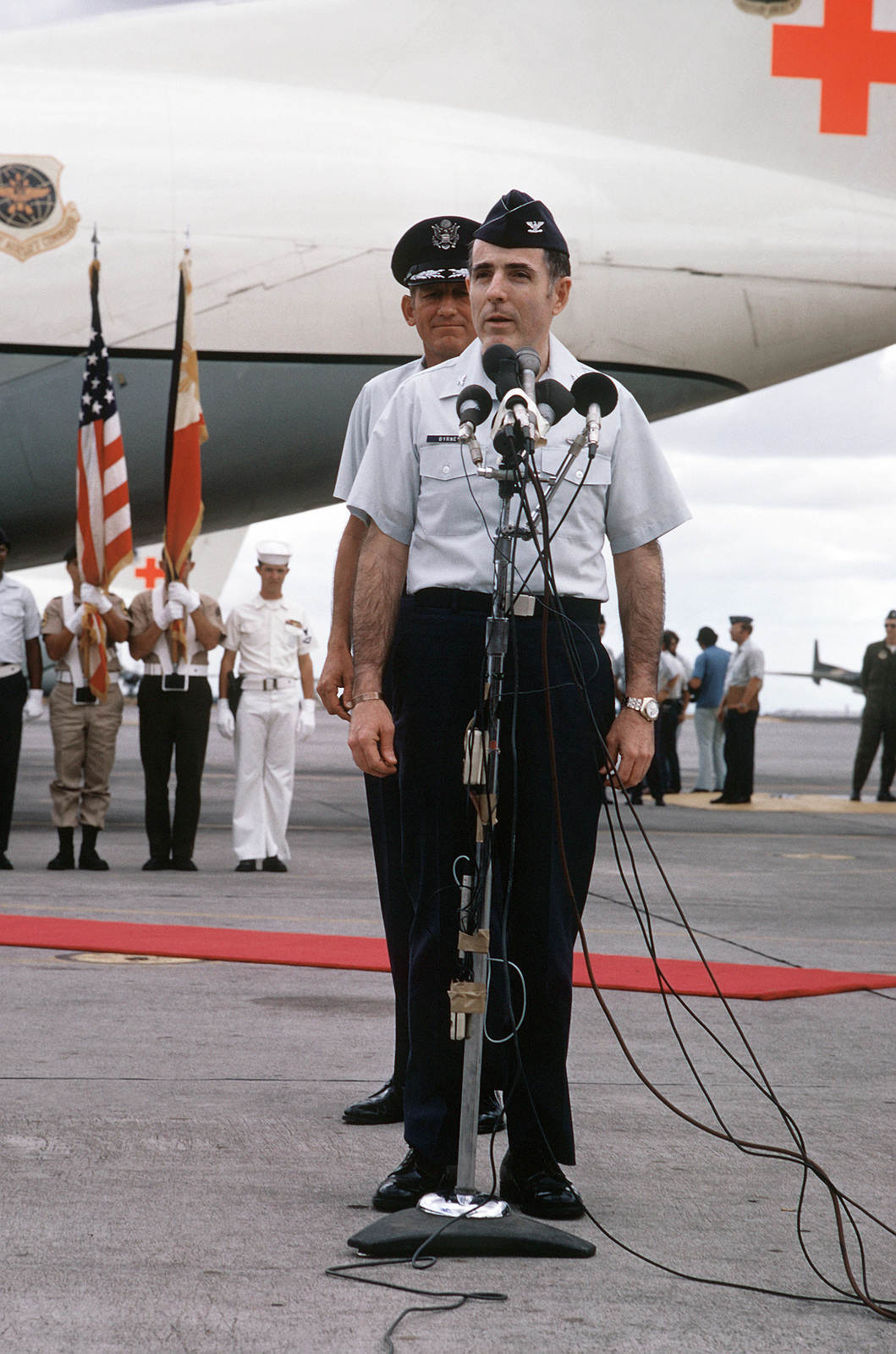 Former POW and U.S. Air Force COL Ronald Edweard Byrne Jr. talks to press and well wishes at microphones prior to boarding the C-141 Starlifter for the flight to sthe states. Behind COL Byrne is LGEN William G. Moore, Commander 13th Air Force. COL Byrne was captured on 29 Aug 65 and was released in Hanoi by the North Vietnamese on 12 Feb 73
