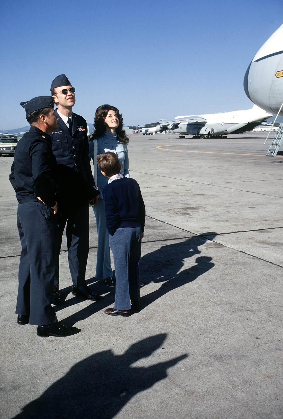 Former POW and U.S. Air Force CPT Darrel Edwin Pyle, wife Karen, son and an escort look over the giant C-5 Galaxy aircraft on the flight line. CPT Pyle was captured on 13 Jun 66 and released by the North Vietnamese in Hanoi on 12 Feb 73