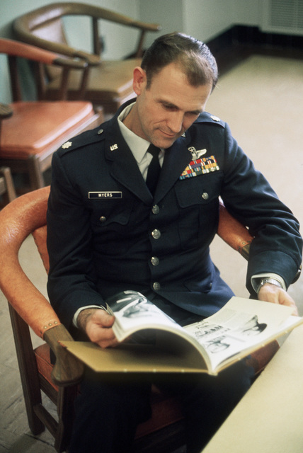 Former POW and U.S. Air Force LCOL Armand Jesse Myers looks through a book on Vietnam prisoners of war in the hospital lounge. LCOL Myers was captured on 1 Jun 66 and released by the North Vietnamese in Hanoi 12 Feb 73