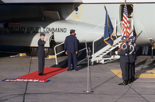 """Former POW and U.S. Air Force LCOL Lewis Wiley Shattuck (Captured 11 Jul 66) salutes the American Flag upon his arrival on the C-141 Starlifter from Clark Air Base, Philippines. In the background MGEN John Gonge, 22nd Air Force Commander and MGEN Daniel """"Chappie"""" James await the next returnee to deplane. LCOL Shattuck was in the first group of POWs released on 12 Feb 73 by the North Vietnamese government in Hanoi"""