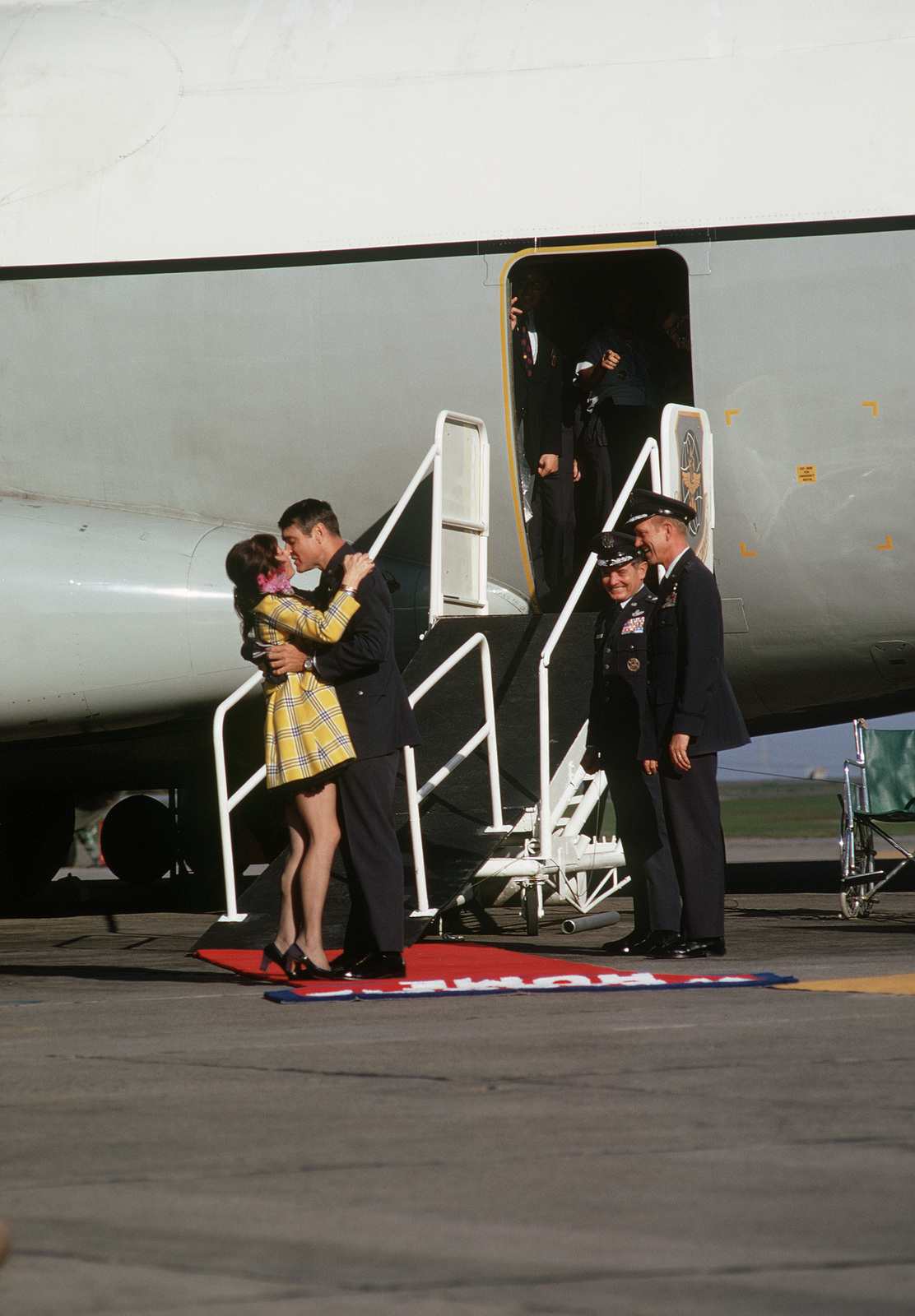 Former POW and U.S. Air Force MAJ Hubert Kelly Flesher kisses his wife at the ramp of the C-141 Starlifter, that transported him and fellow POWs from Clark AB, Philippines. MGEN John Gonge, 22nd Air Force Commander, 22nd AF looks on. MAJ Flesher was captured on 2 Dec 66 and released by the North Vietnamese in Hanoi on 18 Feb 73