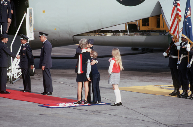 Former POW and U.S. Air Force MAJ Wesley Duane Schierman (Captured 28 Aug 65) hugs his wife, as son and daughter waits, on his arrival. In background MGEN John Gonge, 22nd Air Force Commander and BGEN Ralph Saunders greet another returning ex-POW. MAJ Schierman was released by the North Vietnamese in Hanoi on 12 Feb 73