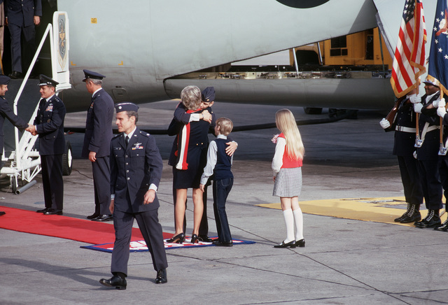 Former POW and U.S. Air Force MAJ Wesley Duane Schierman (Captured 28 Aug 65) hugs his wife, as son and daughter wait, on his arrival. In foreground fellow ex-POW, LCOL Richard Paul Keirn (Captured 24 Jul 65) walks away from the greeting party. Both MAJ Schierman and LCOL Keirn were released by the North Vietnamese in Hanoi on 12 Feb 73