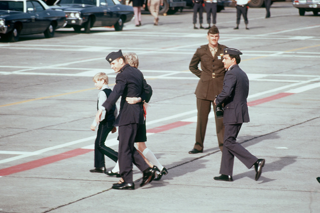 Former POW and U.S. Air Force MAJ Wesley Duane Schierman (Captured 28 Aug 65) walks with his wife, son and daughter across the ramp after arriving from Clark Air Base. MAJ Schierman was released by the North Vietnamese in Hanoi on 12 Feb 73