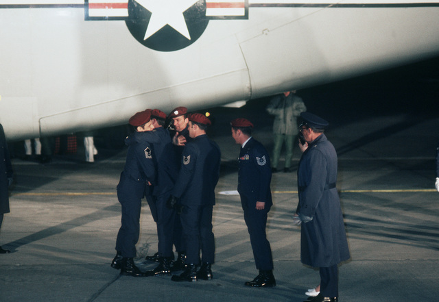 Former POW and U.S. Air Force SMSGT Arthur Cormier (Captured 6 Nov 65) is hugged at planeside by some fellow Pararescuemen who came out to greet the returning former POWs on their nighttime arrival at Scott. SMSGT Cormier was released by the North Vietnamese in Hanoi on 12 Feb 73