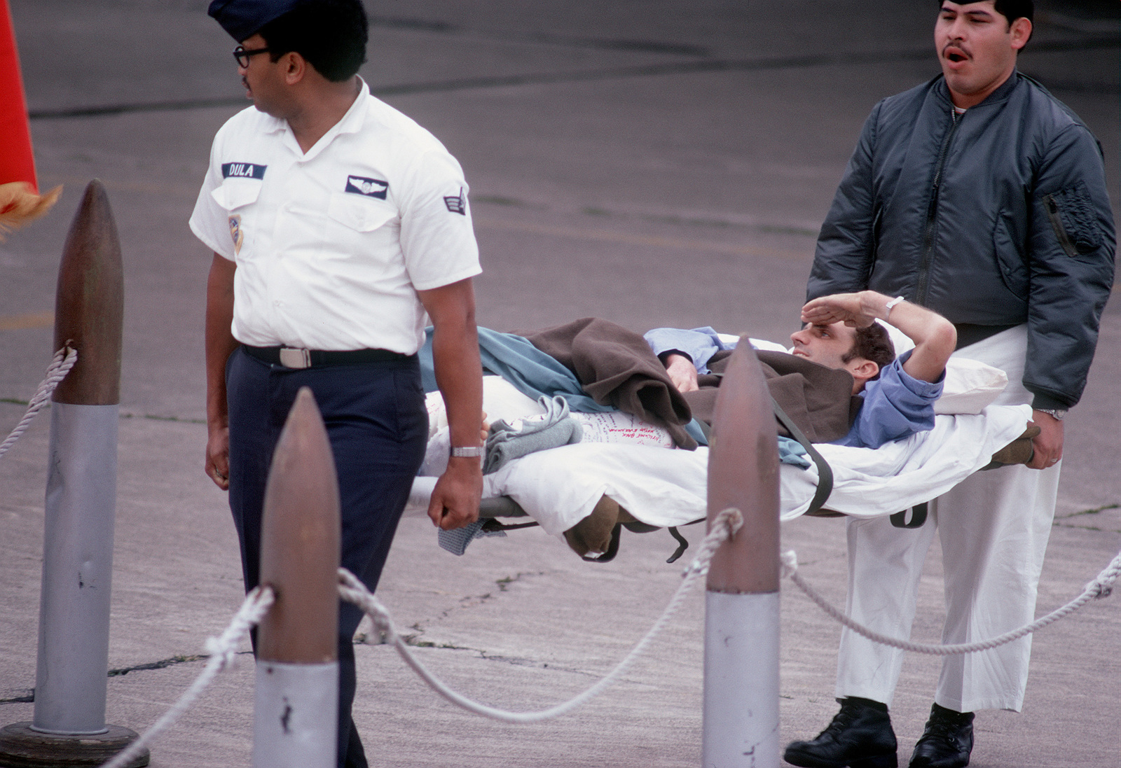Former POW and U.S. Air Force TSGT James R. Cook salutes the colors from his stretcher as he is carried from the C-141 aircraft. TSGT Cook was captured on 21 Dec 72 and released by the North Vietnamese in Hanoi 12 Feb 73