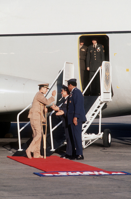 """Former POW and U.S. Navy CMDR Raymond Arthur Vohden (Captured 3 Apr 65), on crutches, salutes MGEN John Gonge, 22nd Air Force Commander and MGEN Daniel """"Chappie"""" James, upon his arrival on the C-141 Starlifter from Clark Air Base, Philippines. CMDR Vohden was in the first group of POWs released on 12 Feb 73 by the North Vietnamese government in Hanoi"""