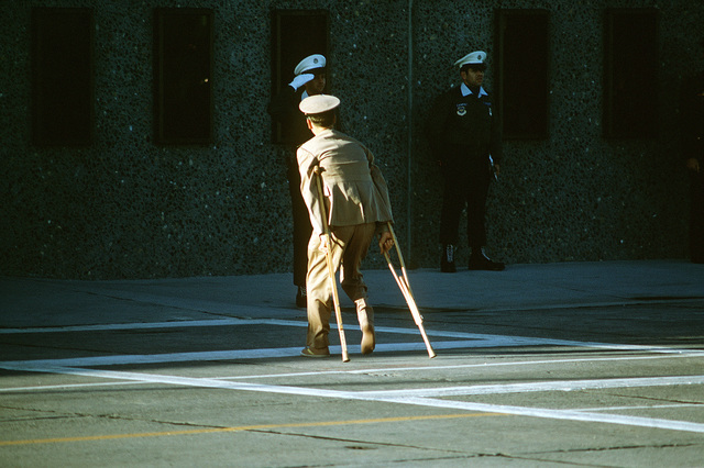 Former POW and U.S. Navy CMDR Raymond Arthur Vohden (Captured 3 Apr 65) uses his crutches to leave the flight line after his arrival from Clark Air Base, Philippines. CMDR Vohden was in the first group of POWs released by the North Vietnamese government in Hanoi