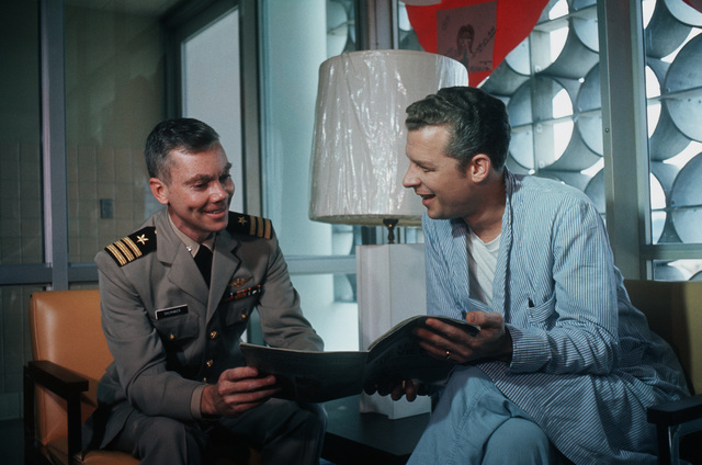 Former POW and U.S. Navy CMDR Robert Harper Shumaker (Captured 11 Feb 65) shares a magazine with fellow ex-POW U.S. Navy LCMDR Phillip Neal Butler (Captured 20 Apr 65) in the hospital reading lounge. CMDR Shumaker and LCMDR Butler were released by the North Vietnamese in Hanoi on 12 Feb 73