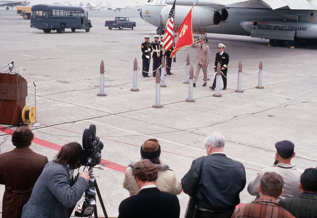 Former POW and U.S. Navy CPT Harry Tarleton Jenkins Jr. salutes the colors as he walks, accompanied by an unidentified Naval officer, from the C-141 Starlifter to the waiting microphones. CPT Jenkins was captured on 13 Nov 65 and released by the North Vietnamese in Hanoi 12 Feb 73