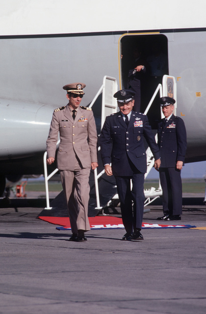 Former POW and U.S.Navy CMDR James Glenn Pirie walks away from the C-141 Starlifter, that transported him and fellow POWs from Clark AB, Philippines, with MGEN John Gonge, 22nd Air Force Commander, BGEN William Deitrich, Vice Commander, 22nd AF in the background. CMDR Pirie was captured on 22 Jun 67 and released by the North Vietnamese in Hanoi on 18 Feb 73