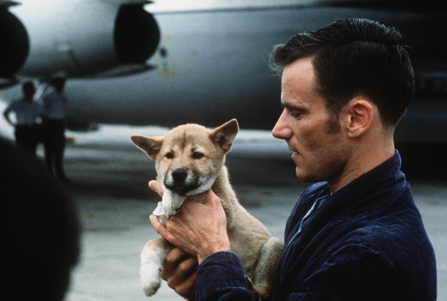 Former Prisoner of War, U.S. Navy LT CMDR Edward Anthony Davis, (CAptured 26 Aug 65) carrying his puppy, MACO, talks to the press prior to his departure for the states. The puppy was given toim by a North Vietnamese guard prior to his release in the second group of POWS from Hanoi on February 12, 1973