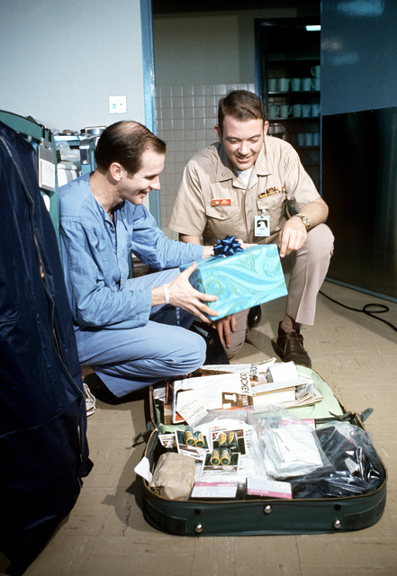 In the Clark AB hospital, released Prisoner of War, U.S. Navy CMDR John Bryan McKamey (Captured 2 June 65) and his escort officer, LT CMDR Gary Stieger share a laugh during the packing of CMDR McKamey's suitcase. CMDR McKamey was in the first group of POWs released by North Vietnam at Hanoi on February 12, 1973