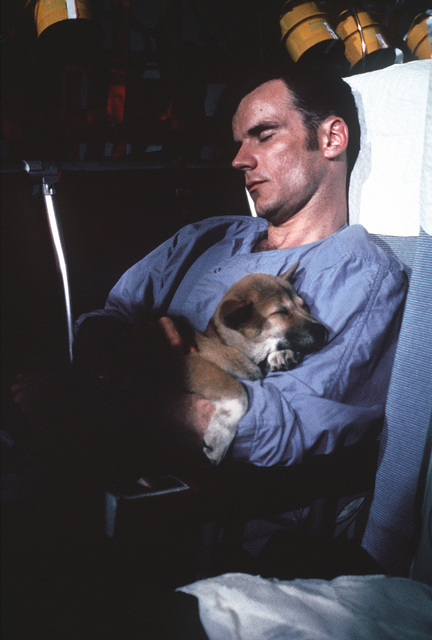 On board a Military Airlift Command's Starlifter, former Prisoners of War, U.S. Navy LT CMDR Edward Anthony Davis, (Captured 26 Aug 65) and his puppy, MACO, catch some well deserved rest after departing Clark Air Base, Philippines. The puppy was given to him by a North Vietnamese guard prior to his release in the second group of POWs from Hanoi on February 12, 1973