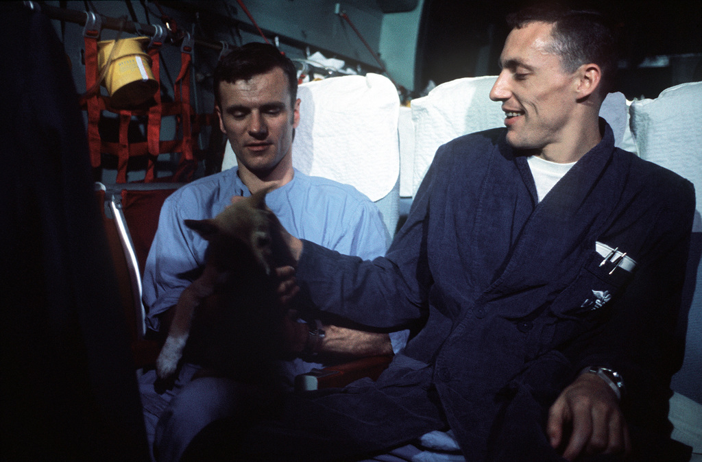 On board a Military Airlift Command's Starlifter, former Prisoners of War, U.S. Navy LT CMDR Edward Anthony Davis, (Captured 26 Aug 65) and LT CMDR Larry Howard Spencer, (Captured 18 Feb 66) after departing Clark Air Base, Philippines. LT CMDR Davis holds the puppy, MACO, that was given to him, by a North Vietnamese guard, prior to his release in the second group on February 12, 1973. LT CMRD Spencer was released with the third group of POWs from Hanoi on February 12, 1973