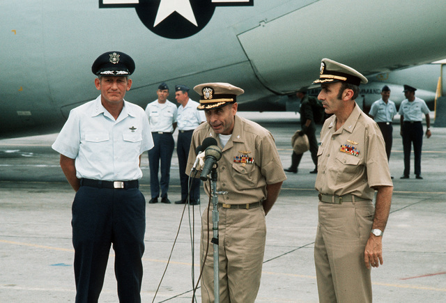 Returned POWs U.S. Navy CPT Jeremiah Andrew Denton (on left), (Captured 18 Jul 65) make a farewell statement at the microphones as fellow ex-POW Navy CPT James Alfred Mulligan, (Captured 20 Mar 66) and 13th Air Force Commander, LGEN William G. Moore listens. Both Denton and Mulligan were released by the North Vietnamese in Hanoi on 12 Feb 73 in Hanoi