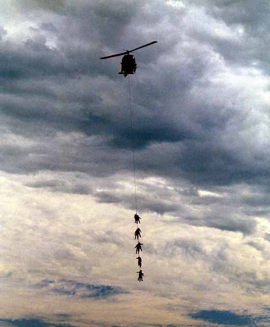 "Ten Marine Corps test jumpers in ""stick"" formation are towed by a UH-1N helicopter during tests of the special patrol insertion/extraction system (SPIE) at the Naval Aerospace Recovery Facility"