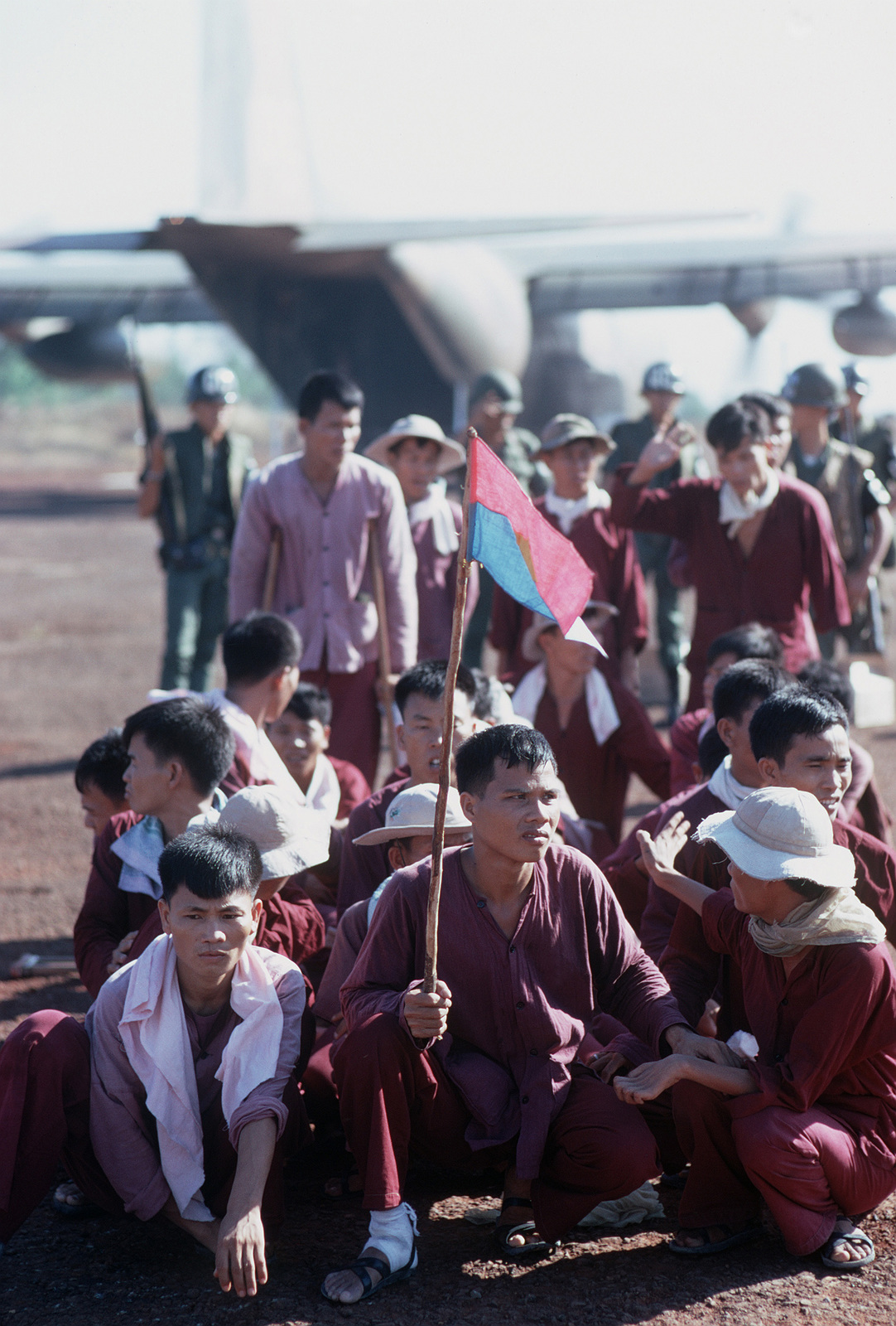 Viet Cong POWs, one with a Viet Cong flag, stand and sit at the exchange location. They were flown in on USAF C-130 aircraft from Bien Hoa Air Base. They will be exchanged for American and South Vietnamese POWs held by the Viet Cong forces