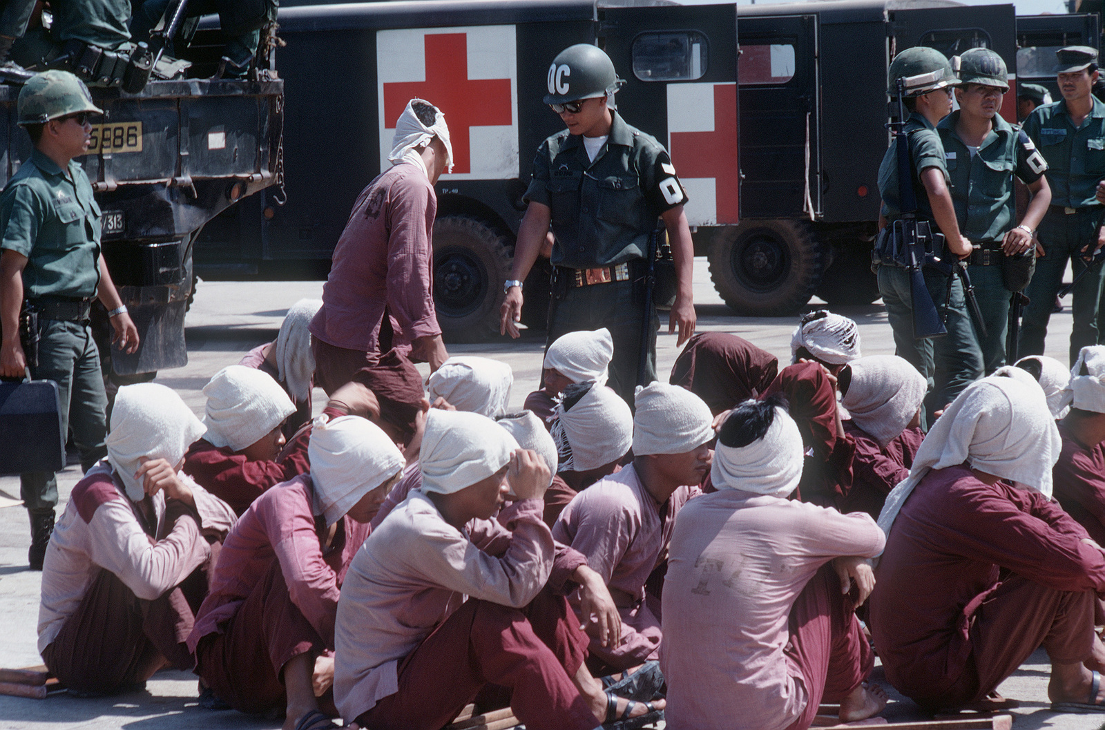 Viet Cong POWs sit on the ramp at Tan Son Nhut Air Base under the watchful eyes of South Vietnamese military police. The POWs will be airlifted to Loc Ninh, South Vietnam for the prisoner exchange between the United States/South Vietnam and North Vietnam/Viet Cong militaries