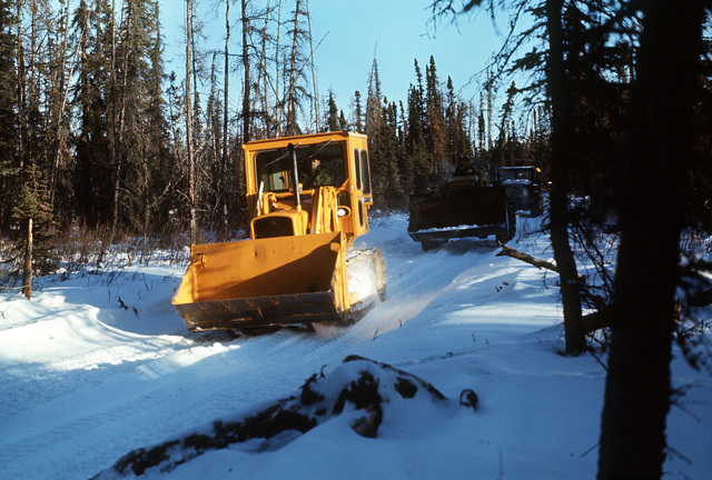 Front-end loaders move through the snow en route to Blair Lakes Range from Clear Creek