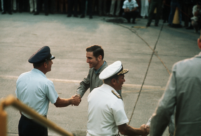 Ex-POW is greeted upon arriving by LGEN William G. Moore Jr., Commander 13th Air Force. On right, Admiral Noel Gaylor, Commander Pacific Command greets another returnee