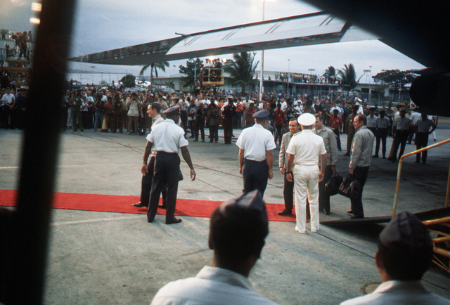 Four Ex-POWs are greeted upon arriving, after the flight from Hanoi, North Vietnam, by (Left to Right) Unidentified Air Force CMSGT, LGEN William G. Moore Jr., Commander 13th Air Force and Admiral Noel Gaylor, Commander Pacific Command