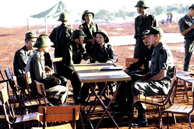 On a barren field near Loc Ninh BGEN Stan McClellan, U.S. Army, CHIEF of STAFF, Military Assistance Command - Vietnam (MACV) discusses the pending exchange of American and South Vietnamese prisoners for Viet Cong (VC) and North Vietnamese (NVA)prisoners with Viet Cong negotiators