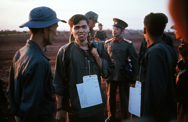 SGT Felix V. Neco-Quinones, U.S. Army, (Captured 16 Jul 68) stands with other POWs, Viet Cong and North Vietnamese military during the POW exchange. He is one of the twenty eight American POWs who were released by the Viet Cong on February 12, 1973