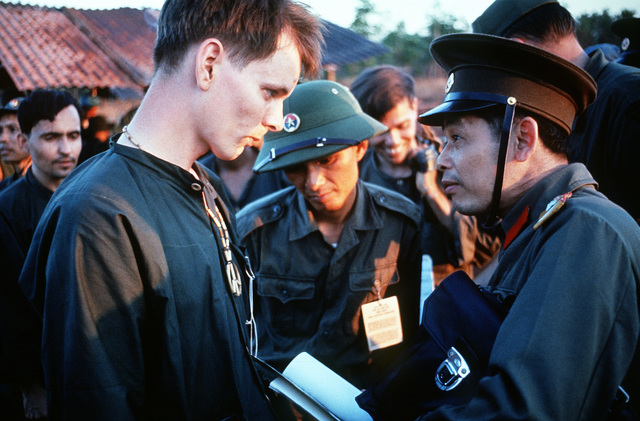 SPC-4 Richard Springman, U.S. Army, Captured 25 May 70) talks with a North Vietnamese Army officer who is looking at his peace symbol. He is one of the twenty eight American POWs who were released by the Viet Cong on February 12, 1973