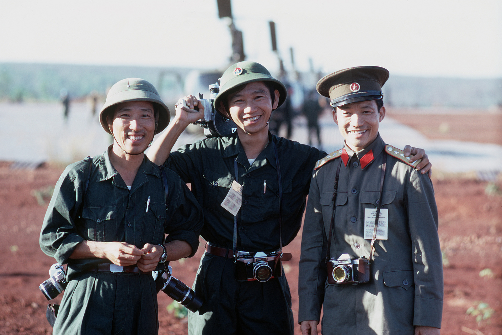 Two Viet Cong and a North Vietnamese Army officer with still and motion picture cameras that they will use to photograph the exchange of prisoners of war