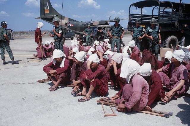 Viet Cong POWs sit on the ramp at Tan Son Nhut Air Base under the watchful eyes of South Vietnamese military police. The POWs were brought to the airbase in the 6X6 trucks in the background and will be airlifted to Loc Ninh, South Vietnam on the C-123 transport aircraft for the prisoner exchange between the United States/South Vietnam and North Vietnam/Viet Cong militaries