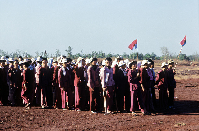 Viet Cong POWs stand in formation, two of their members carry the Viet Cong flag, after being flown in from Bien Hoa. They will be exchanged for American and South Vietnamese POWs held by the Viet Cong forces