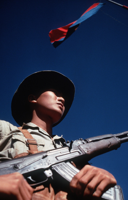 Viet Cong soldier stands beneath a Viet Cong flag carrying his AK-47 rifle. He was participating in the exchange of POWs by the Four Power Joint Military Commission