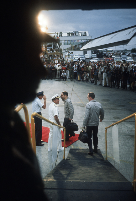 View from inside the C-141 as two Ex-POWs are greeted upon arriving, after the flight from Hanoi, North Vietnam, by (Left to Right) LGEN William G. Moore Jr., Commander 13th Air Force and Admiral Noel Gaylor, Commander Pacific Command