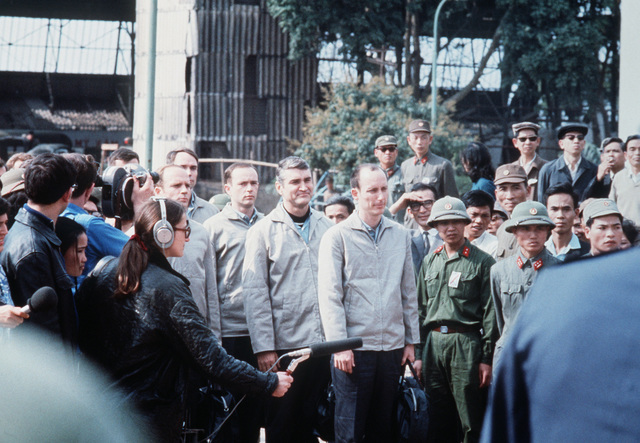 American POWs lined up at Gia Lan Airport, surrounded by North Vietnamese military, public and press, prior to being turned over to the U.S. delegation. (Left to Right) U.S. Air Force CPT Michael Christopher Lane (Captured 2 Dec 66), partially hidden behind CPT Lane, USAF CPT John Walter Clark (Captured 12 Mar 67), USAF CPT John Owen Davies (Captured 4 Feb 67), USAF MAJ Hubert Kelly Flesher (Captured 2 Dec 66) and USAF CPT Herbert Benjamin Ringsdorf (Captured 11 Nov 66)
