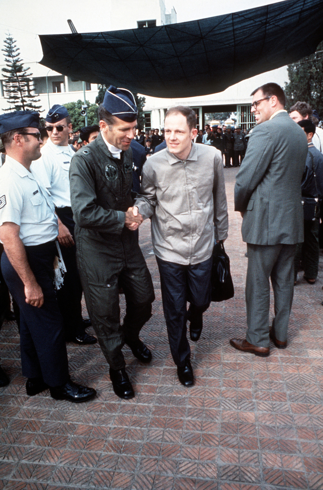 At Gia Lan Airport, surrounded by North Vietnamese and American officials, the press and public, just released, ex-POW U.S. Navy LCMDR Joseph C. Plumb Jr., (Captured 19 May 67) walks to meet his escort officer for the trip to Clark Air Base