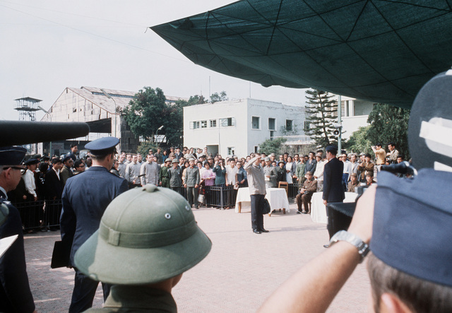 At Gia Lan Airport, surrounded by North Vietnamese and American officials, the press and public, just released, ex-POW U.S. Air Force CPT John H. Nasmyth Jr. (Captured 4 Sep 66), salute COL Emil J. Wengel, a member of the American delegation
