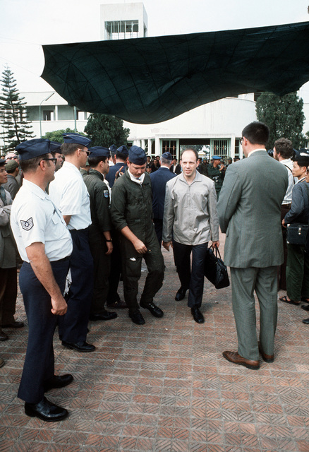 At Gia Lan Airport, surrounded by North Vietnamese and American officials, the press and public, an unidentified, just released ex-POW walks with his escort to the waiting C-141 transport for the trip to Clark Air Base
