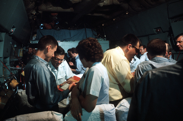 Released POWs enjoy their first taste of freedom on the flight between Hanoi, North Vietnam and Clark Air Base, Philippines. On left, ex-POW U.S. Air Force MAJ Joseph S. Abbott Jr. looks at photo of his family, on the cover of TIME magazine, with one of the flight nurses. Dr. Roger Shields, State Dept representative is standing on the right